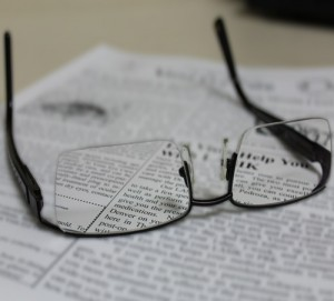 A pair of glasses sits on top of a newspaper.
