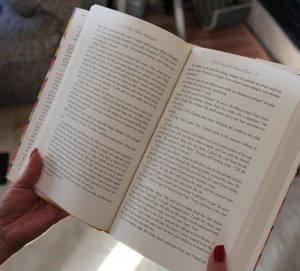 A person holds a book up to be read.