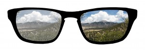 Polarization example showing a pair of glasses: the lens on the left is hazy and indistinct, while the right polarized, lens has good contrast and no haze.