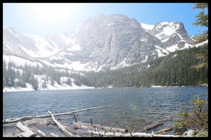 A view of a mountain lake with a bright, glare-inducing sun overhead.