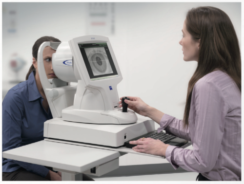 We use corneal topography to carefully measure the microscopic curves of the cornea.  This image shows a technician guiding a patient into the instrument.