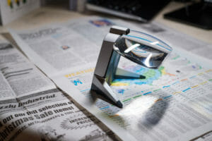 A lighted stand magnifier is used to read the weather report in the newspaper.