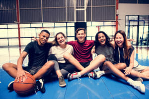 A group of kids sits on a basketball court eager to play a game.