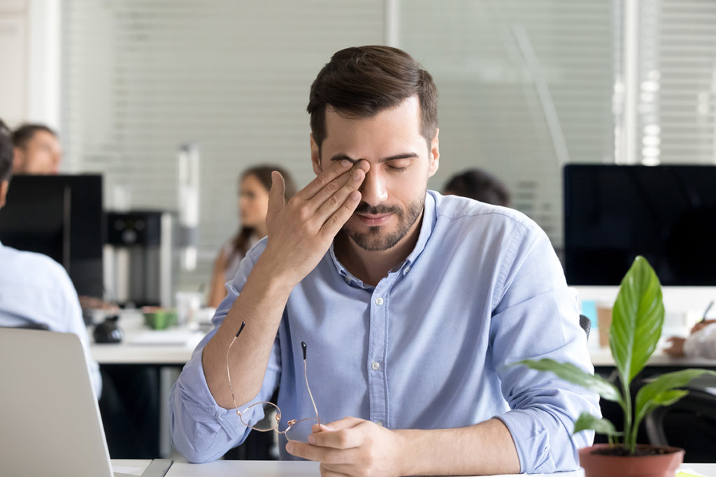 A man working at a laptop pauses from his tasks to rub at his tired eye.